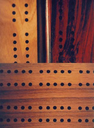 a close up of the holes on several cribbage boards